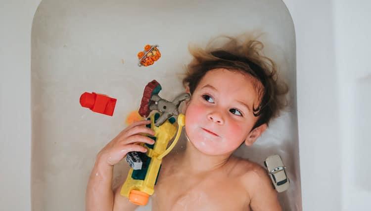 Kind spielt in der Badewanne